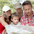 Stock Photo: Family looking at map on a hiking day