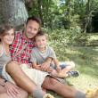 Father sitting by a tree with his children — Stock Photo