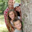 Smiling family standing behind a tree — Stock Photo #18263485