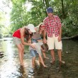 Family crossing a river — Stock Photo #18263575