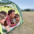 Parents and children in camp tent - Stock Photo