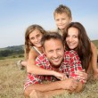 Closeup of happy family lying in grass — Stock Photo