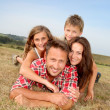 Closeup of happy family lying in grass — Stock Photo #18263943