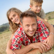 Closeup of happy family lying in grass — Stock Photo #18263953