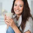 Closeup of beautiful woman with hot drink at home — Stock Photo