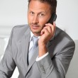 Closeup of businessman talking on mobile phone — Stock Photo