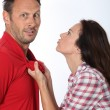 Angry woman pulling boyfriend shirt neck - Stock Photo