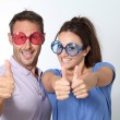 Couple wearing colored glasses having fun — Stock Photo #18264877