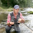 Stock Photo: Fishermin river with fly fishing rod