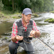 Foto Stock: Fishermin river with fly fishing rod