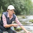 Woman with fly fishing rod in river — Stock Photo