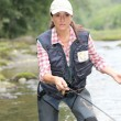 Womwith fly fishing line in river — Stockfoto #18265303