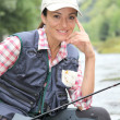 Fisherwoman sitting on stones in river with fishing rod — Stock Photo