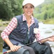 Stock Photo: Fisherwomsitting on stones in river with fishing rod