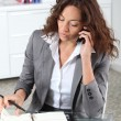 Businesswoman on the phoen writing on agenda — Stock Photo