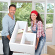 Couple holding furniture in their new home — Stock Photo #18265947