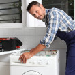 Plumber fixing broken washing machine — Stock Photo