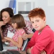 Teacher and children learning to use computer - Stockfoto