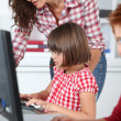 Teacher and children learning to use computer — Stock Photo #18266127