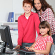 Stock Photo: Teacher and children learning to use computer
