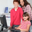 Teacher and children learning to use computer — Stock Photo #18266211