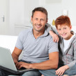 Man and child at home with laptop computer — Stock Photo
