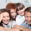 Happy family of 4 laying on a sofa at home — Foto de Stock
