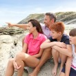 Parents and children sitting by the sea — Stock Photo