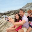 Father taking picture of the family in front of the sea - Stok fotoğraf