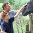 Parents and children petting horses in countryside — Stockfoto