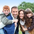 Parents doing piggyback to their children in countryside — Stock Photo