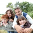 Family leaning on a fence - Stockfoto