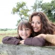 Mother and daughter leaning on a fence - Stok fotoğraf