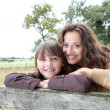Mother and daughter leaning on a fence - Stockfoto