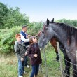 Parents and children petting horses in countryside - Stock fotografie