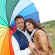 Smiling couple on a raining day - Stok fotoğraf