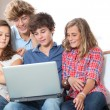 Group of teenagers at home with laptop — Stock Photo
