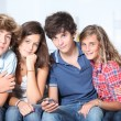 Group of teenagers at home with music player — Stock Photo