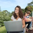 Teenagers sitting outside with laptop computer — Stock Photo #18268639