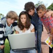 Teenagers sitting outside with laptop computer - Foto de Stock