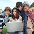 Teenagers sitting outside with laptop computer — Stock Photo
