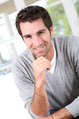 Smiling man with hand on chin — Stock Photo