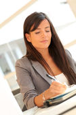 Portrait of beautiful businesswoman writing notes on agenda — Stok fotoğraf