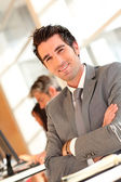 Portrait of smilng businessman with arms crossed — Stock Photo