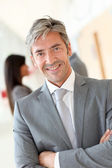 Portrait of handsome businessman standing in hall — Stock Photo
