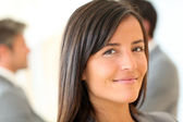 Portrait of beautiful businesswoman standing in front of group — Stock Photo