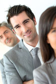 Smiling businessman standing amongst group — Stock Photo