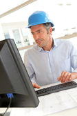 Engineer in office working on construction plan — Stock Photo
