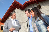 Real-estate agent showing house under construction to couple — Stock Photo