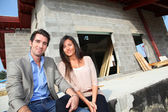 Happy couple sitting in front of house under construction — Stock Photo